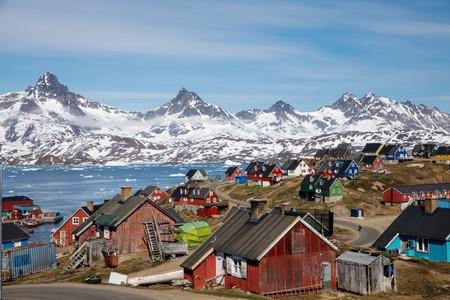 FILE PHOTO: Snow covered mountains rise above the harbour and town of Tasiilaq