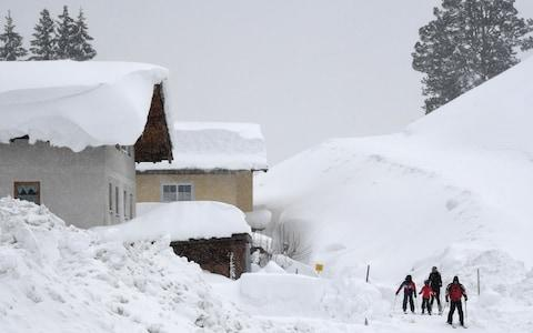 Skiers make their way through the streets after heavy snowfall in the small village of Filzmoos, Austria - Credit: Christof Stache/AFP
