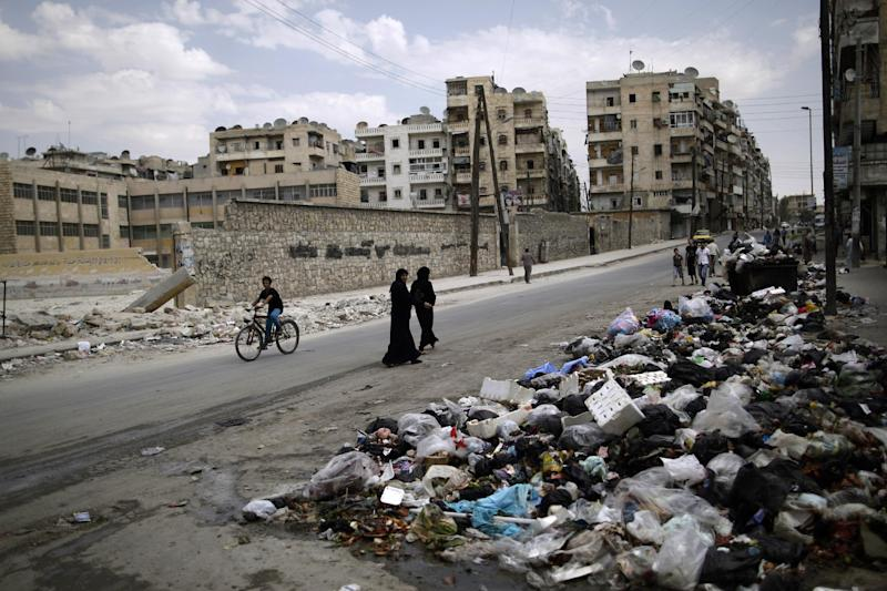 A Syrian woman looks back while walking with another woman past a pile of garbage left on a roadside in Aleppo, Syria, Tuesday, Sept. 11, 2012. (AP Photo/Muhammed Muheisen)