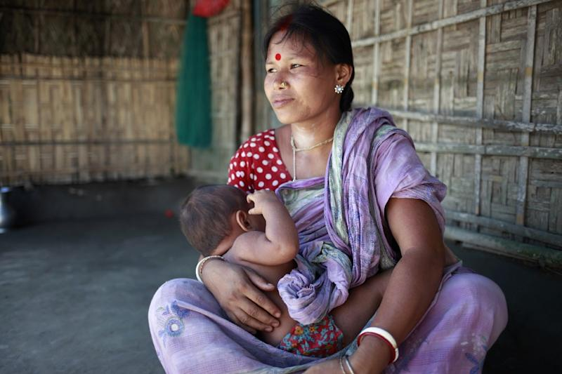 Binodini Rani Barman, feeds her one-year-old son Labonno outside of their home in Dalaha-Khagrabari in the Bangladeshi district of Panchagarh, on July 30, 2015 (AFP Photo/Suvra Kanti Das)