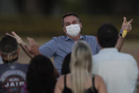 FILE - in this July 24, 2020 file photo, Brazil's President Jair Bolsonaro, who is infected with COVID-19, wears a protective face mask as he talks with supporters during a Brazilian flag retreat ceremony outside his official residence the Alvorada Palace, in Brasilia, Brazil. The South American nation proud of its role as a regional leader in science, technology and medicine, finds itself falling behind its neighbors in the global race for immunization against a pandemic that has already killed nearly 200,000 of its people. (AP Photo/Eraldo Peres, File)