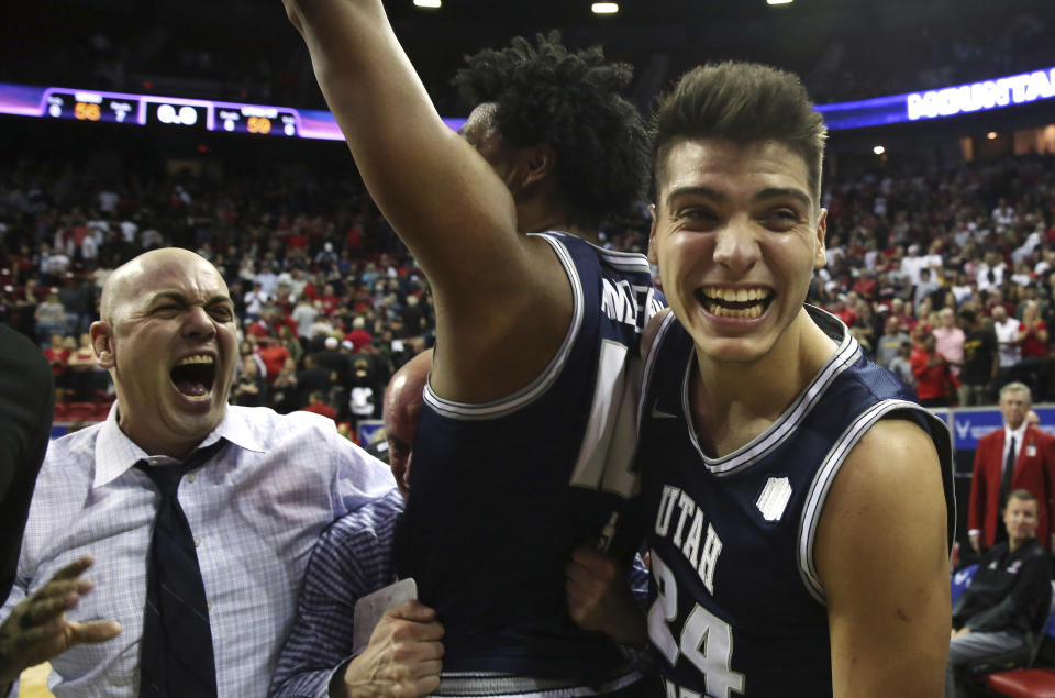 Utah State head coach Craig Smith, left, with players Alphonso Anderson, center, and Diogo Brito (24) celebrate following an NCAA college basketball game against San Diego State for the Mountain West Conference men's tournament championship Saturday, March 7, 2020, in Las Vegas. (AP Photo/Isaac Brekken)