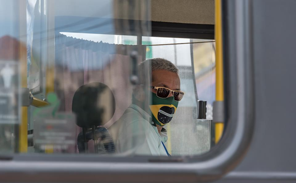 Recife downtown, Pernambuco, Brazil - June 11, 2020:Bus driver working with a brazilian flag themed mask due to Covid- 19.