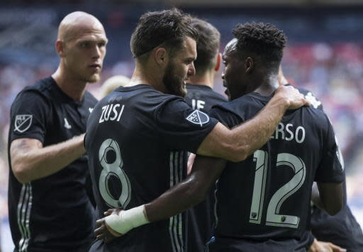 Sporting Kansas City's Graham Zusi (8), Gerso Fernandes (12) and Botond Barath, back left, celebrate after the Vancouver Whitecaps scored an own goal during the first half of an MLS soccer match Saturday, July 13, 2019, in Vancouver, British Columbia. (Darryl Dyck/The Canadian Press via AP)