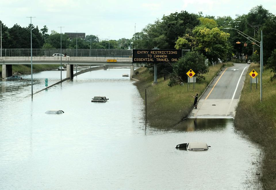 Detroit residents on June 28 observe a stretch of I-94 that is still under several feet of water following heavy weekend rains which flooded parts of Metro Detroit. (Matthew Hatcher/SOPA Images/LightRocket via Getty Images)