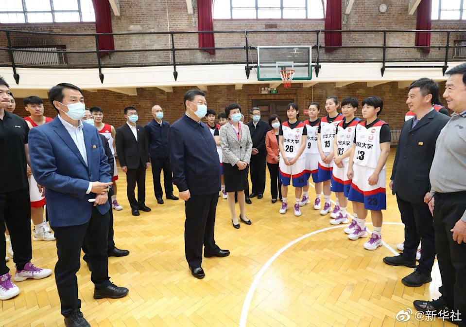 Xi meets a basketball team during his visit. Photo: Weibo