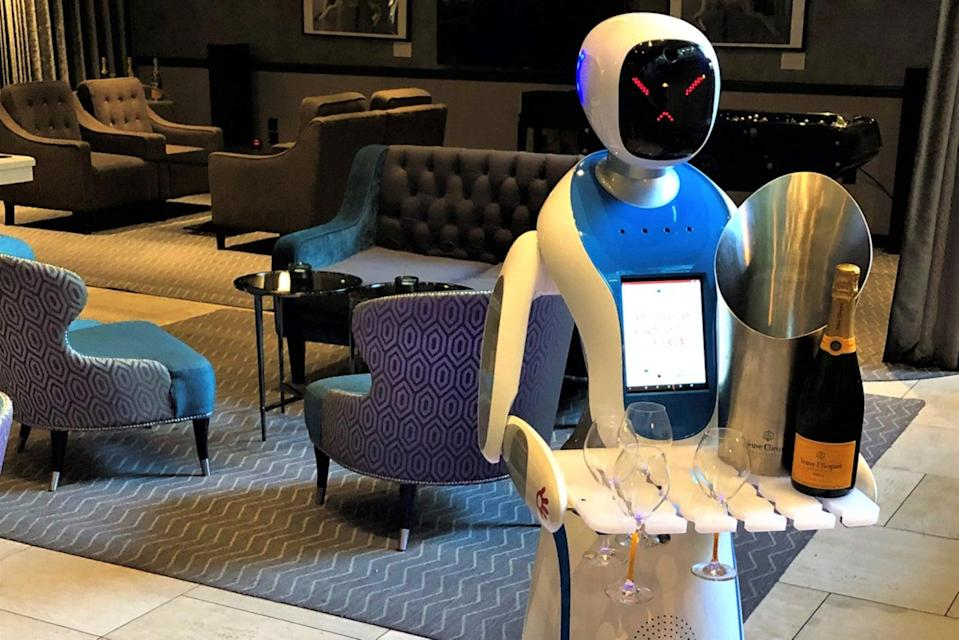 <p>Bots bearing gifts: the machine may have an unhappy face, but it does at least deliver bottle of bubbly</p> (M Restaurants)