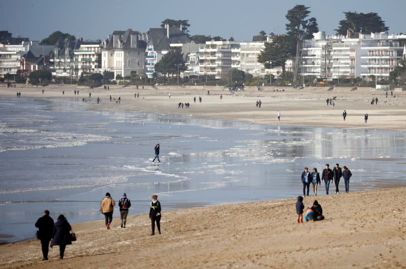 People walk on the beach of La Baule