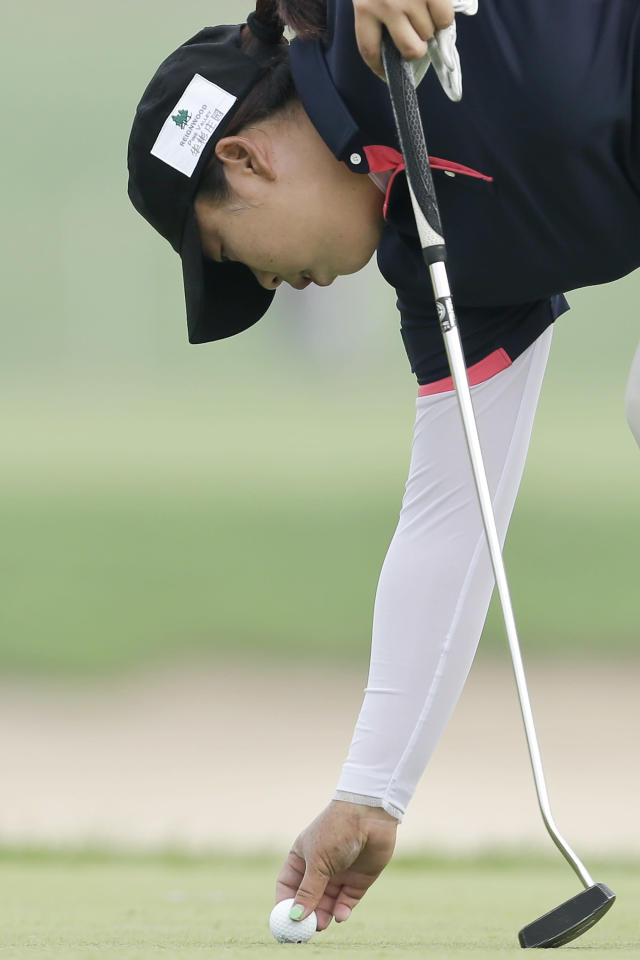 China's Shanshan Feng sets her ball down on the third green during the second round of the Reignwood LPGA Classic golf tournament at Pine Valley Golf Club on the outskirts of Beijing, China, Friday, Oct. 4, 2013. (AP Photo/Alexander F. Yuan)