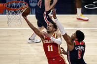 Atlanta Hawks guard Trae Young (11) lays in a bucket as Washington Wizards forward Rui Hachimura (8) defends during the first half of an NBA basketball game Wednesday, May 12, 2021, in Atlanta. (AP Photo/Butch Dill)
