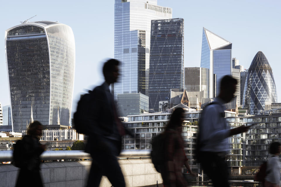 UK, London, blurred motion of incidental business people walking to work with view of the financial district behind