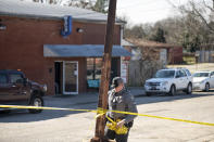A law enforcement officer removes crime scene tape in front of Mac's Lounge, the scene of an early morning bar shooting, Sunday, Jan. 26, 2020, in Hartsville, S.C. (AP Photo/Sean Rayford)