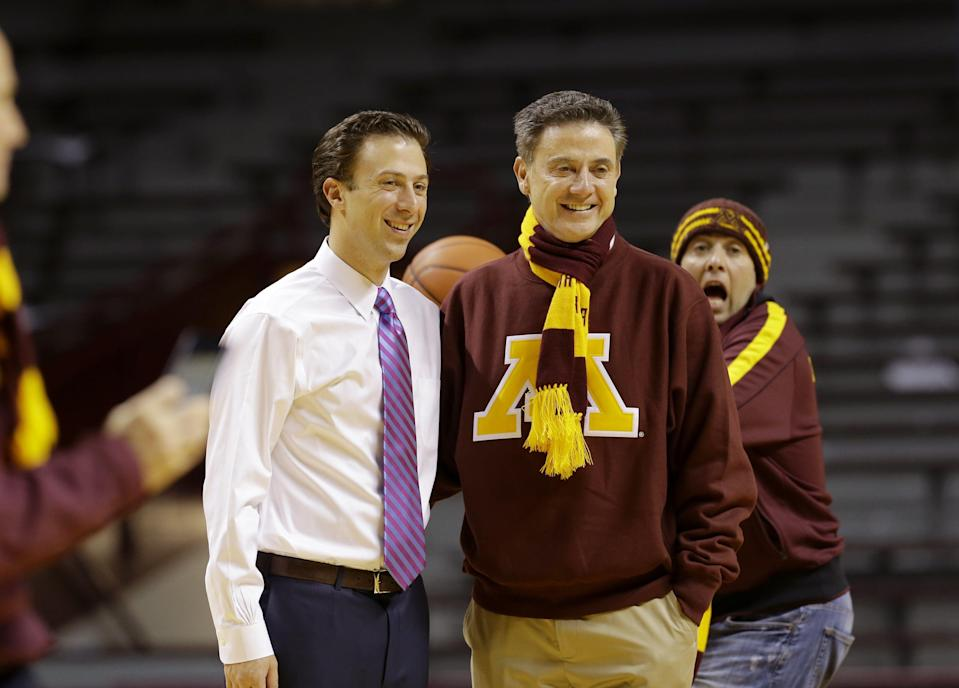 Louisville head coach Rick Pitino, right, poses with his son and Minnesota head coach, Richard Pitino, left, for the team photographer as son Michael Pitino photobombs them following an NCAA college basketball game between Minnesota and South Dakota State in Minneapolis, Tuesday, Dec. 10, 2013. Minnesota won 75-59. (AP Photo/Ann Heisenfelt)