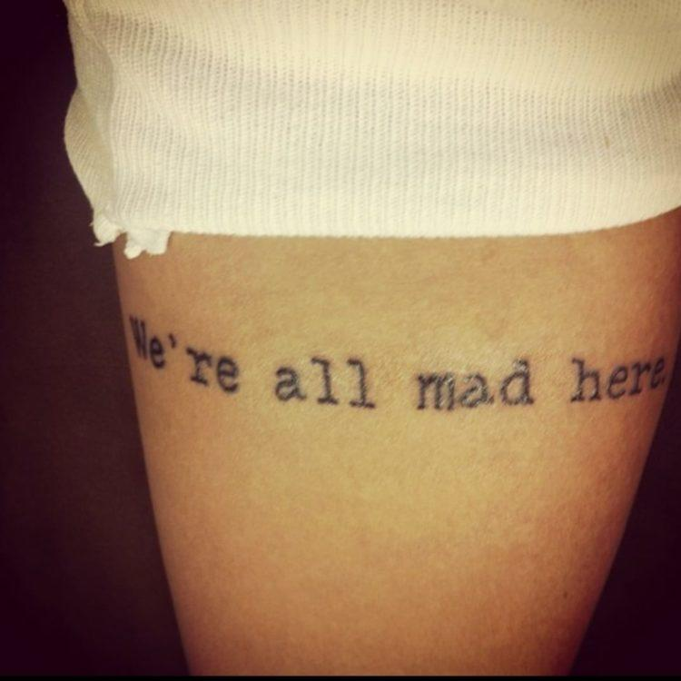 "Melissa shows the viewer a tattoo that reads, ""We're all mad here."" It is located on her arm."