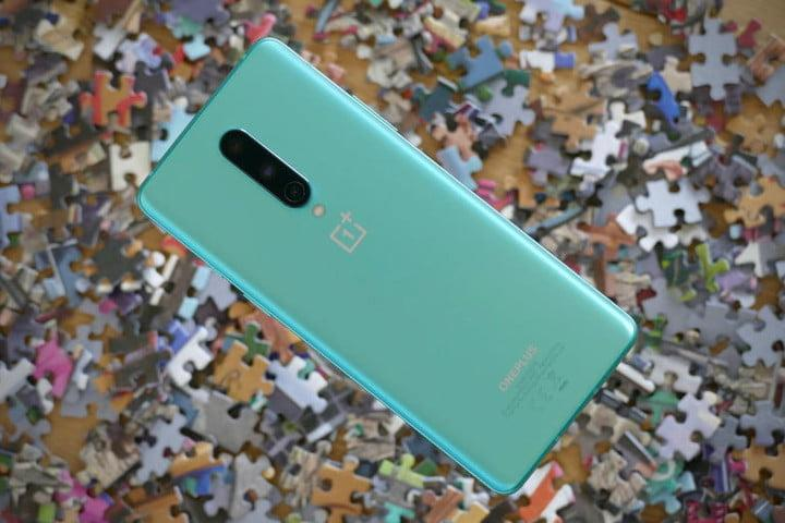 image of the OnePlus 8 seen from behind, in light blue, with a background full of puzzle pieces