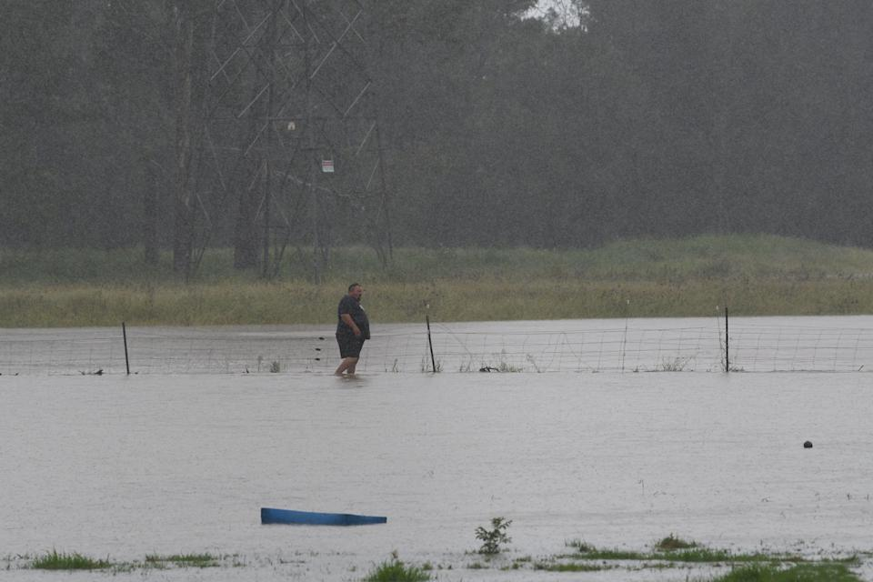 Farmers on Grange Road in Schofield tend to the stock due to heavy rain in Sydney on Saturday. Source: AAP