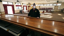 With chairs stacked against the wall of their hall space, Craig DeOld, commander at Veterans of Foreign War Post #1018, poses at the empty bar rail at the post's rental space, Monday, March 15, 2021, in Boston. Local bars and halls run by the VFW and American Legion posts have fallen on hard times during the coronavirus pandemic. Organizers say many risk permanent closure after states ordered them, like other bars and halls, to shutter last spring. (AP Photo/Charles Krupa)