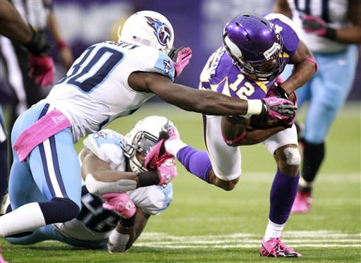 Minnesota Vikings wide receiver Percy Harvin, right, runs from Tennessee Titans' Jason McCourty, left, and Akeem Ayers, center, after making a reception during the first half of an NFL football game on Sunday, Oct. 7, 2012, in Minneapolis. The Vikings won 30-7. (AP Photo/Genevieve Ross)