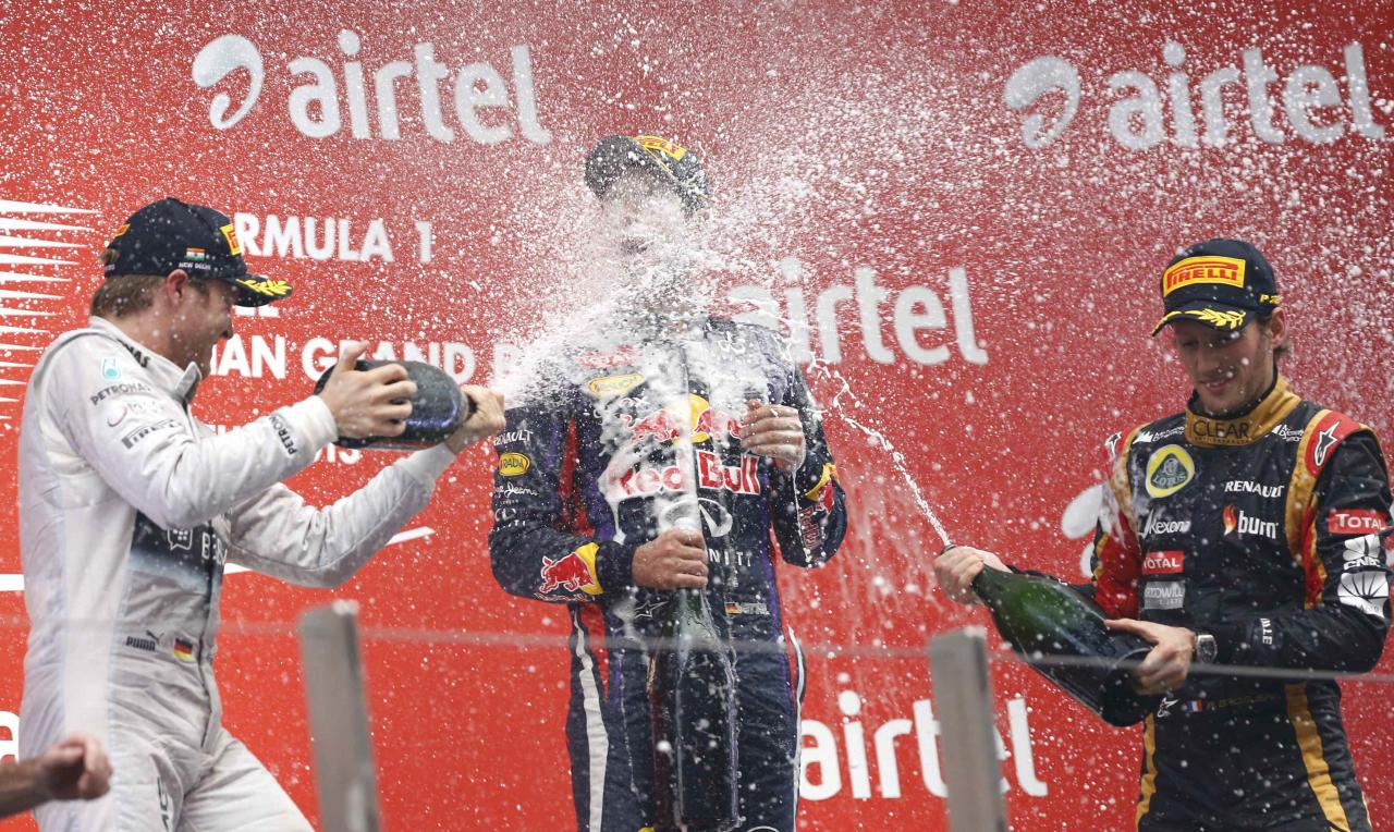Mercedes Formula One driver Nico Rosberg of Germany (L) and Lotus F1 Formula One driver Romain Grosjean (R) of France spray champagne on the face of Red Bull Formula One driver Sebastian Vettel of Germany on the podium after the Indian F1 Grand Prix at the Buddh International Circuit in Greater Noida, on the outskirts of New Delhi, October 27, 2013. 