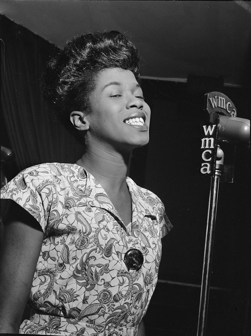 """<p>Jazz singer Sarah Vaughan (aka """"Sassy"""" or """"The Divine One"""") has been described as having one of """"the most wondrous voices of the 20th century"""" <a href=""""http://www.allmusic.com/artist/sarah-vaughan-mn0000204901/biography"""" rel=""""nofollow noopener"""" target=""""_blank"""" data-ylk=""""slk:by music critic Scott Yanow"""" class=""""link rapid-noclick-resp"""">by music critic Scott Yanow</a> — and we won't argue. <a href=""""https://www.youtube.com/watch?v=yJ-9IBZaydQ"""" rel=""""nofollow noopener"""" target=""""_blank"""" data-ylk=""""slk:In a now-iconic live recording made in Europe in 1964"""" class=""""link rapid-noclick-resp"""">In a now-iconic live recording made in Europe in 1964</a>, Vaughan took the stage nervously """"with a cold,"""" but the moment she began singing the classic tune """"Misty,"""" the audience was transcended into musical bliss. She was a class act — always immaculately made up and wearing in stylish, form-fitting dresses. <i>(Photo: Getty Images)</i></p>"""