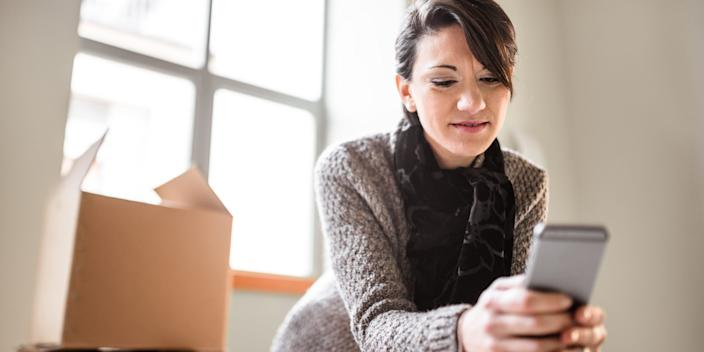 woman holding phone with packages tracking