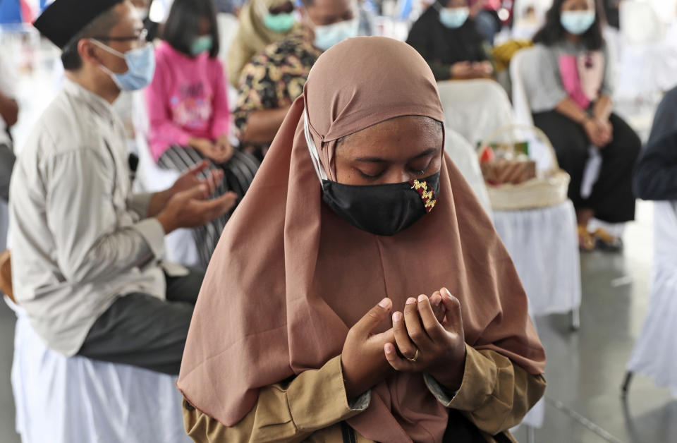 A relative weeps while she prays during a memorial ceremony for the victims of Sriwijaya Air flight SJ-182, on the deck of Indonesian Navy Ship KRI Semarang that sails in the Java Sea where the plane crashed on Jan. 9 killing all of its passengers, near Jakarta in Indonesia, Friday, Jan. 22, 2021. (AP Photo/Tatan Syuflana)