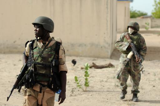 Nigerian soldiers patrol in the north of Borno state close to a former Boko Haram camp on June 5, 2013 near Maiduguri