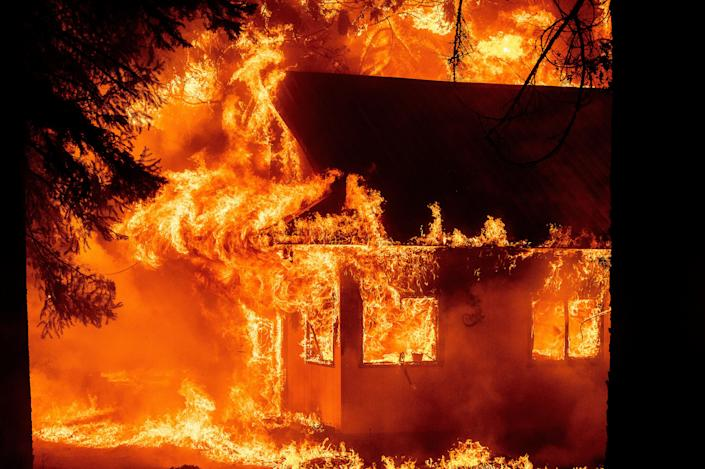 Flames consume a home as the Dixie Fire tears through the Indian Falls community in Plumas County, Calif., on Saturday, July 24, 2021.