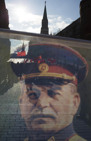 Communist supporters, unseen, carry a portrait depicting Soviet dictator Josef Stalin as they line up to place flowers on Stalin's grave in Red Square, outside the Kremlin wall to mark the 60th anniversary of his death, Moscow, Russia, Tuesday, March 5, 2013. Stalin led the Soviet Union from 1924 until his death in 1953. Communists credit him with leading the country to victory in World War II while others condemn the brutal purges that killed millions. (AP Photo/Alexander Zemlianichenko)