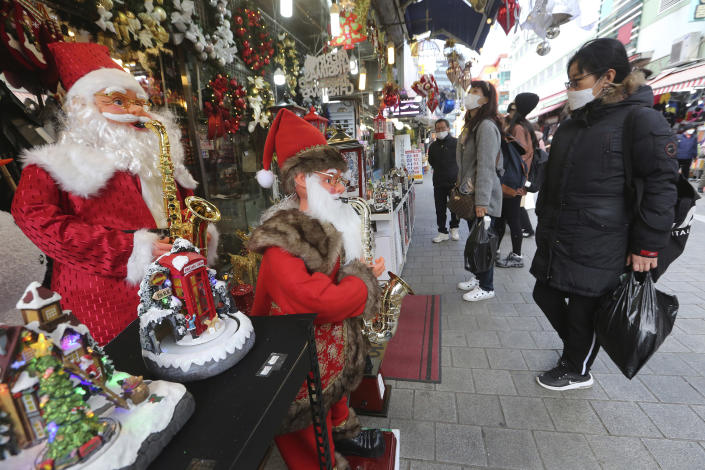 People wearing face masks as a precaution against the coronavirus watch Christmas decorations at a store in Seoul, South Korea, Friday, Nov. 27, 2020. South Korea's daily virus tally hovered above 500 for the second straight day, as the country's prime minister urged the public to stay home this weekend to contain a viral resurgence. (AP Photo/Ahn Young-joon)