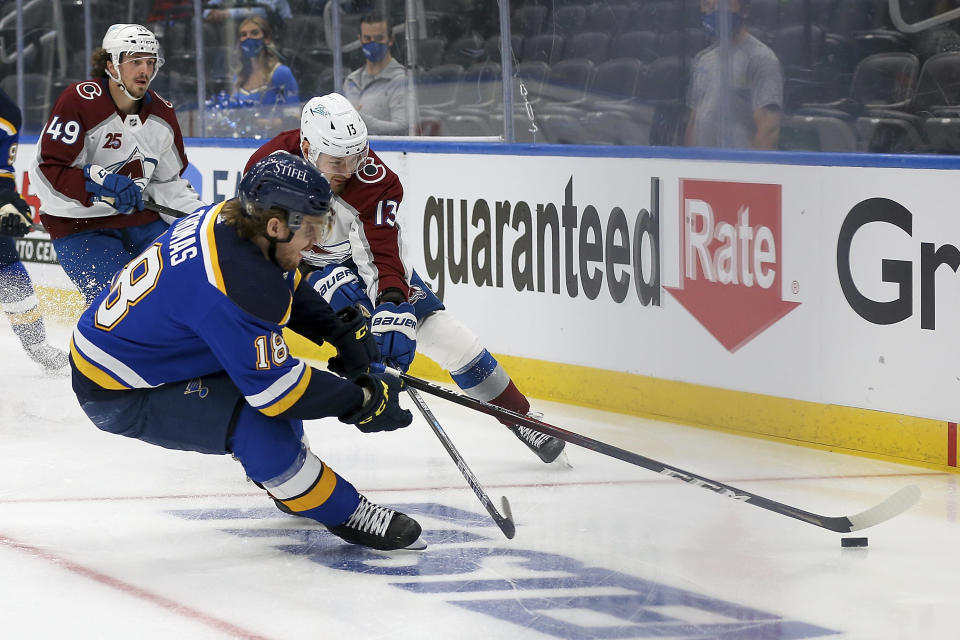St. Louis Blues' Robert Thomas (18) and Colorado Avalanche's Valeri Nichushkin (13) vie for control of the puck during the second period in Game 3 of an NHL hockey Stanley Cup first-round playoff series Friday, May 21, 2021, in St. Louis. (AP Photo/Scott Kane)