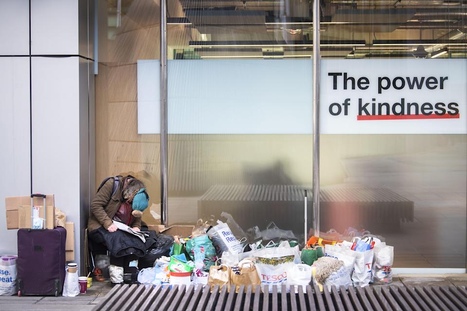 <p>A homeless person sits next to a window in the City of London</p> (PA)