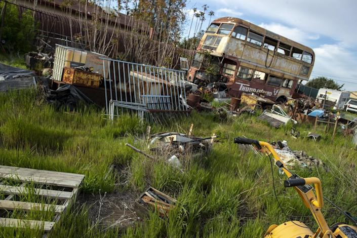 A weedy field strewn with old cars, junk and antiques.