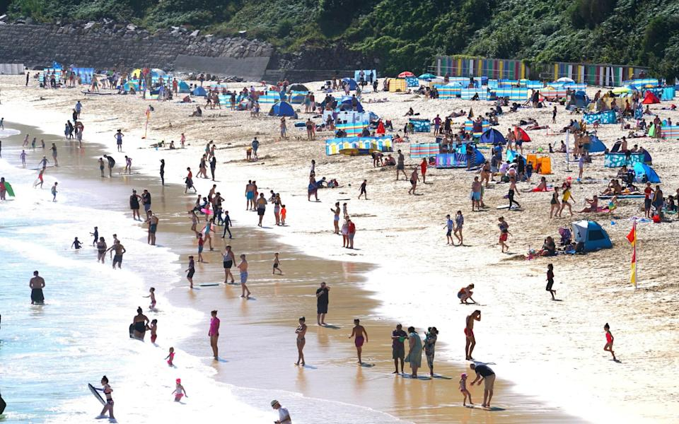 Groups of people relax on the beach in the sun on August 9, 2020 in St Ives, Cornwal - Hugh Hastings / Getty