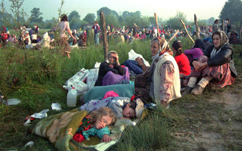 FILE — This July 14, 1995 file photo shows refugees from the overrun U.N. safe haven enclave of Srebrenica who had spent the night outdoors, gathering outside the U.N. base at Tuzla airport. U.N. judges on Tuesday, June 8, 2021 deliver their final ruling on the conviction of former Bosnian Serb army chief Radko Mladic on charges of genocide, war crimes and crimes against humanity during Bosnia's 1992-95 ethnic carnage. Nearly three decades after the end of Europe's worst conflict since World War II that killed more than 100,000 people, a U.N. court is set to close the case of the Bosnian War's most notorious figure. (AP Photo/Darko Bandic, File)