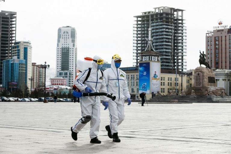 Health workers spray disinfectant in Sukhbaatar square in Ulaanbaatar in March 2020. The country has just recorded its first local transmissions of the coronavirus