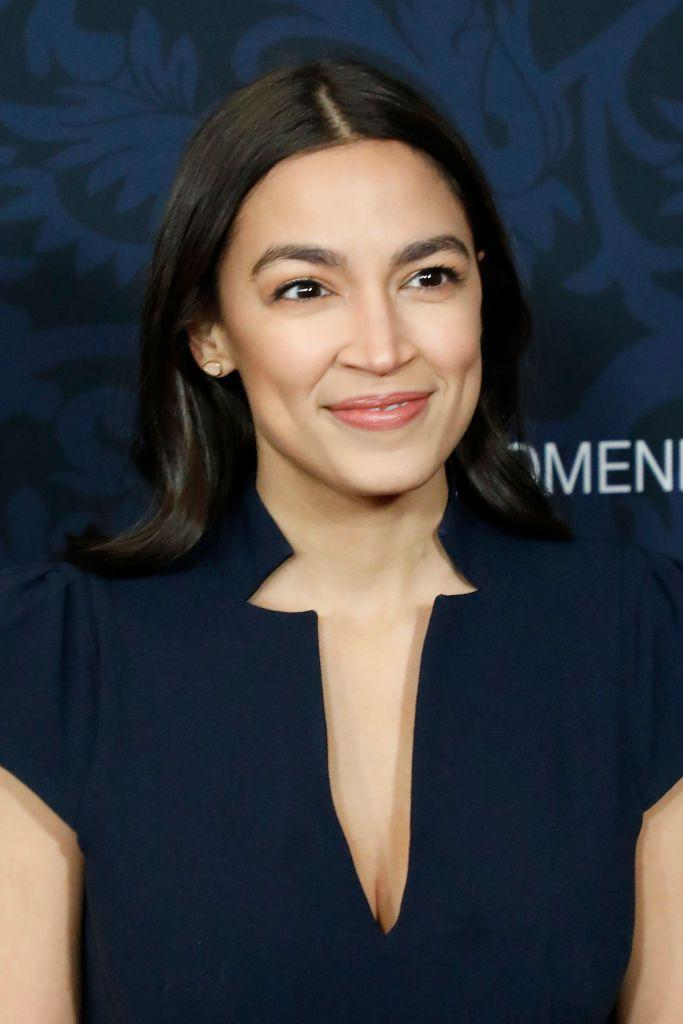 """<p>In 2018, AOC made waves when she ran for New York's 14th Congressional District and won. The then-29-year-old became the <a href=""""https://www.vox.com/2018/11/6/18070704/election-results-alexandria-ocasio-cortez-wins"""" rel=""""nofollow noopener"""" target=""""_blank"""" data-ylk=""""slk:youngest woman ever elected"""" class=""""link rapid-noclick-resp"""">youngest woman ever elected</a> to the U.S. Congress. From the start, the Bronx native of Puerto Rican descent has openly spoken about working as a <a href=""""https://www.newsweek.com/alexandria-ocasio-cortez-republicans-just-waitress-ivanka-trump-tweet-1446752"""" rel=""""nofollow noopener"""" target=""""_blank"""" data-ylk=""""slk:waitress and bartender"""" class=""""link rapid-noclick-resp"""">waitress and bartender</a> to make ends meet. Her experience embodies the very definition of the American dream, and it's helped her connect with the people she represents.</p>"""