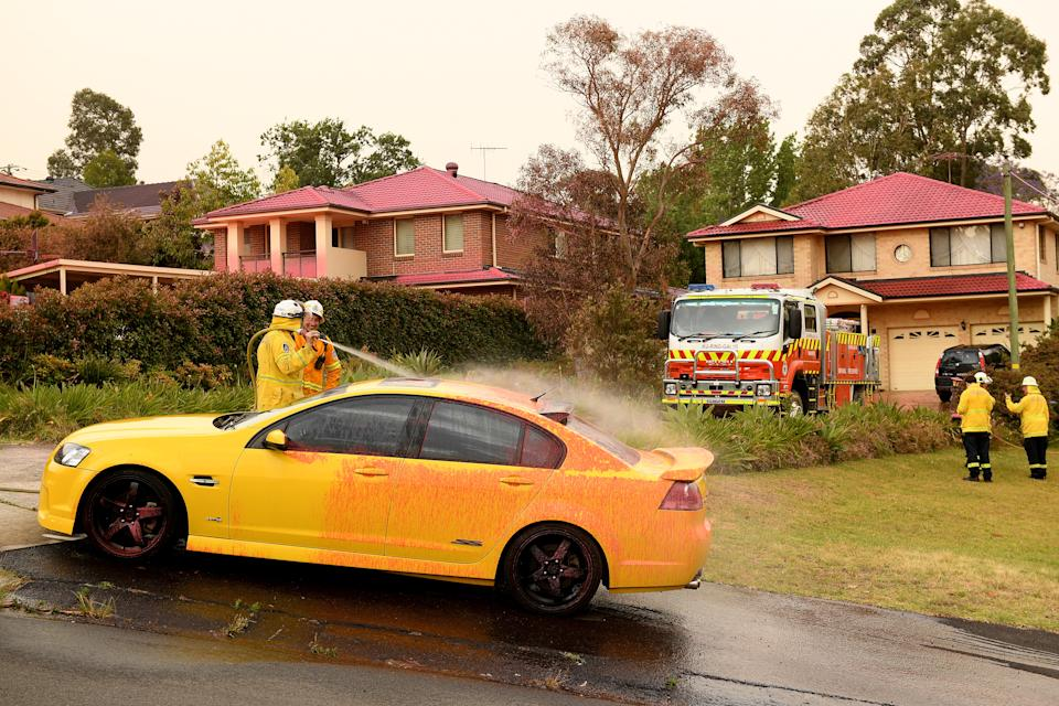 Picture of fire-fighters hosing down cars and driveways to remove the fire retardant, which was used to help ease fires in Sydney's north on Tuesday.