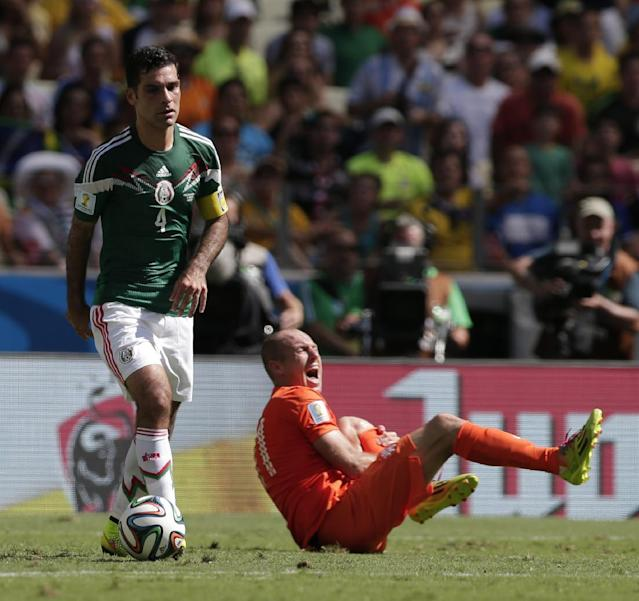Mexico's Rafael Marquez controls the ball as Netherlands' Arjen Robben, right, grimaces during the World Cup round of 16 soccer match between the Netherlands and Mexico at the Arena Castelao in Fortaleza, Brazil, Sunday, June 29, 2014. (AP Photo/Marcio Jose Sanchez)