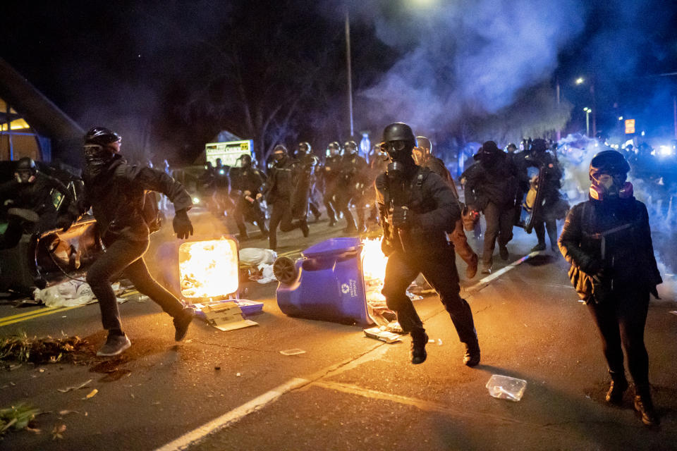 Portland police officers chase protesters during a riot in the wake of Daunte Wright's death.