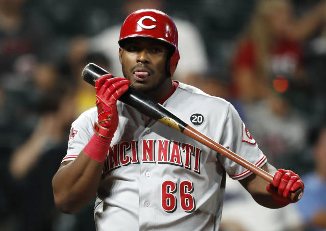 Cincinnati Reds' Yasiel Puig licks his bat after fouling off a pitch from Colorado Rockies relief pitcher Bryan Shaw in the ninth inning of a baseball game Saturday, July 13, 2019, in Denver. The Reds won 17-9. (AP Photo/David Zalubowski)
