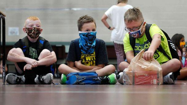 PHOTO: Elementary school students wearing masks to prevent the spread of COVID-19 wait for classes to begin in Godley, Texas, Aug. 5, 2020. (Lm Otero/AP)