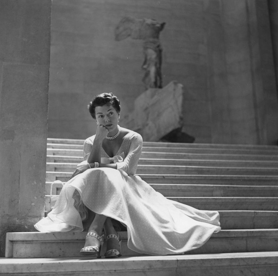 """<p>Actress and pinup model Lana Turner wears pearls and an elegant dress on the steps of the historic Daru staircase at the Louvre Museum. Behind her is the """"Winged Victory of Samothrace"""" sculpture—a marble statue of Greek goddess Nike dating back to the 2nd century BC.</p>"""