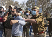 Indian police detain an activist of Peoples Democratic party (PDP) protesting against India's new land laws that allows any Indian citizen to buy land in the disputed region in Srinagar, Indian controlled Kashmir, Thursday, Oct. 29, 2020. Until last year, Indians were not allowed to buy property in the region. But in August 2019, Prime Minister Narendra Modi's government scrapped the disputed region's special status, annulled its separate constitution, split the region into two federal territories. (AP Photo/Mukhtar Khan)