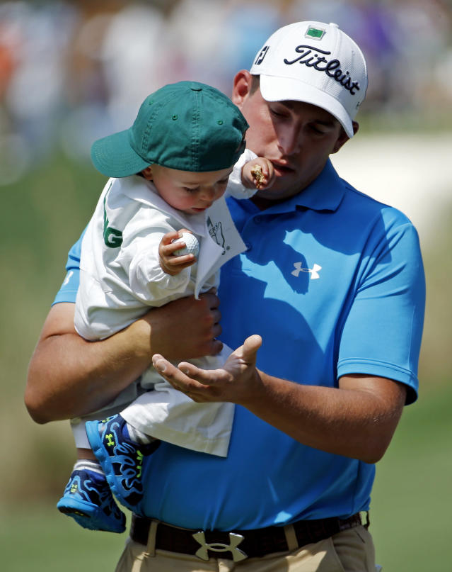Scott Stallings gets a golf ball from his son Finn during the par three competition at the Masters golf tournament Wednesday, April 9, 2014, in Augusta, Ga. (AP Photo/Matt Slocum)
