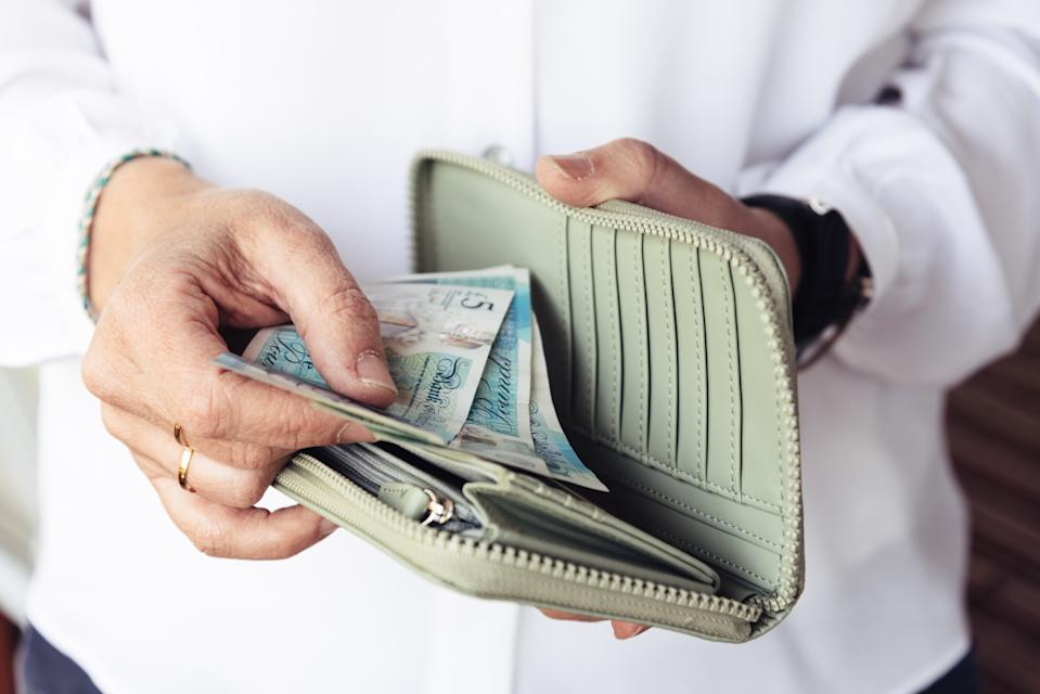 Close up of hand of woman taking out pounds from her purse