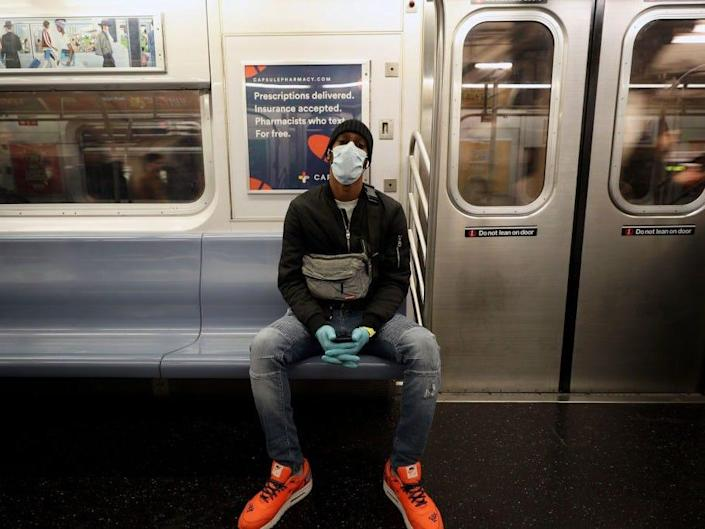 A man wears a face mask and surgical gloves to prevent Covid-19 spread, at the New York City subway train in New York, United States on March 11, 2020.