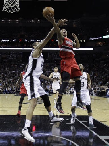 Portland Trail Blazers' Damian Lillard, right, shoots over San Antonio Spurs' Tim Duncan, left, during the first half of an NBA basketball game on Friday, March 8, 2013, in San Antonio. (AP Photo/Eric Gay)