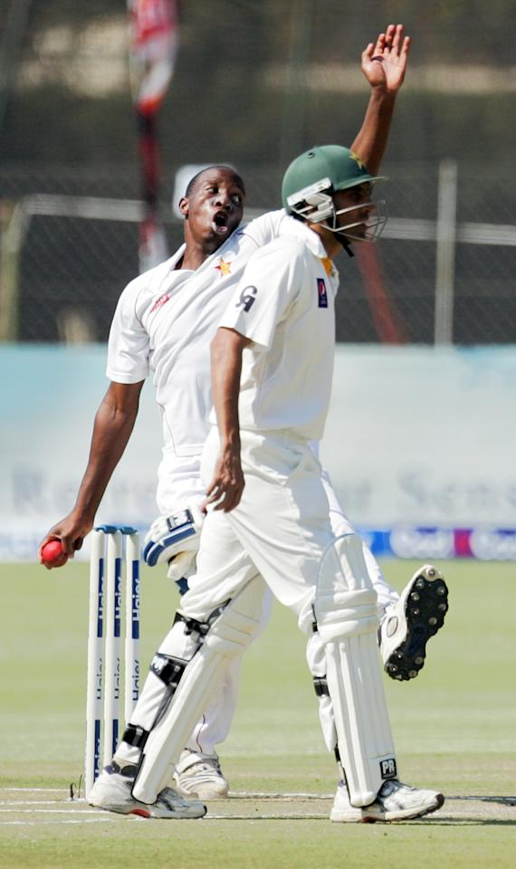 Zimbabwe bowler Shingirirayi Masakadza is in action next to Younis Khan during the fourth day of the first cricket test match between Pakistan and hosts Zimbabwe at the Harare Sports Club September 6, 2013. AFP PHOTO / JEKESAI NJIKIZANA        (Photo credit should read JEKESAI NJIKIZANA/AFP/Getty Images)