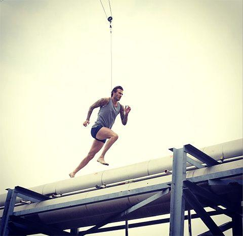 David Beckham takes a running leap across a rooftop. Photo: H&M Instagram.